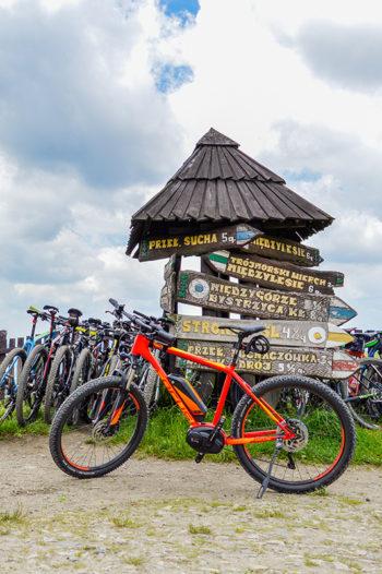 Focus na skrzyżowaniu szlaków turystycznych. W tle tablica informacyjna oraz inne, rowery.
