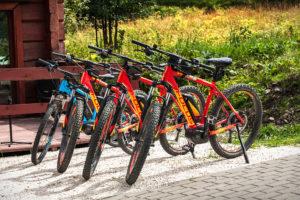 Trzy pomarańczowe modele roweru FOCUS oraz jeden niebieski, również elektryczny