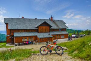 Pomarańczowy elektryczny rower górski przy schronisku na Śnieżniku.